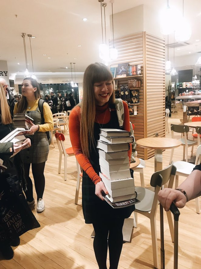 Photo of a girl laughing and holding a big pile of books