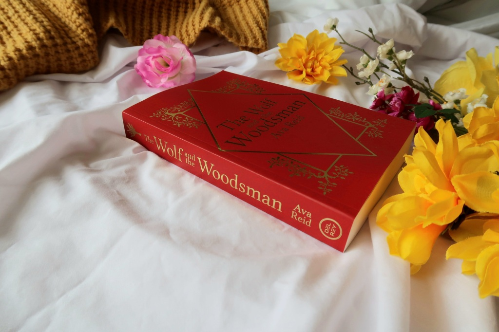 Photo of a proof copy of The Wolf and the Woodsman by Ava Reid, a red book with gold writing