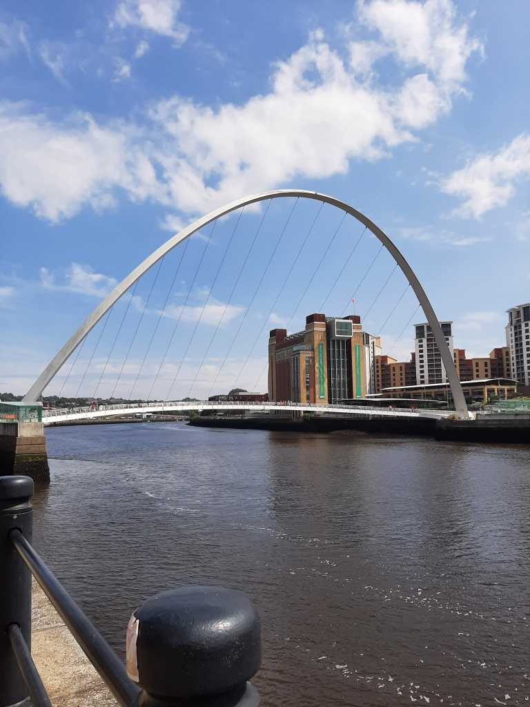 A photo of Newcastle, showing the Millenium bridge set against blue sky and the Baltic art gallery in the background.
